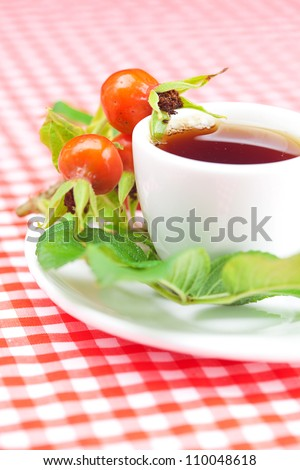 cup of tea and rosehip berries with leaves on plaid fabric