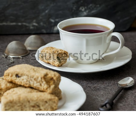 Cup of tea and saucer with biscuits on the table