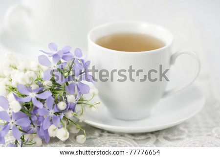 Cup of tea and spring flowers - stock photo