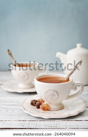 Cup of tea and sugar with teapot over blue background - stock photo