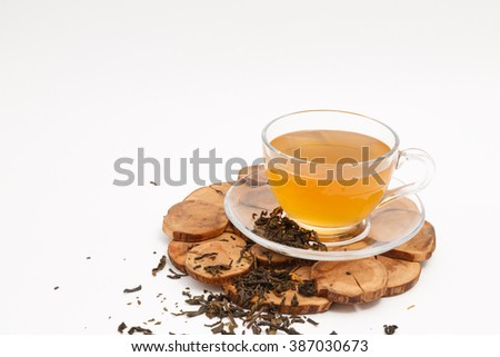 cup of tea and tea leaves on a stand on a white background