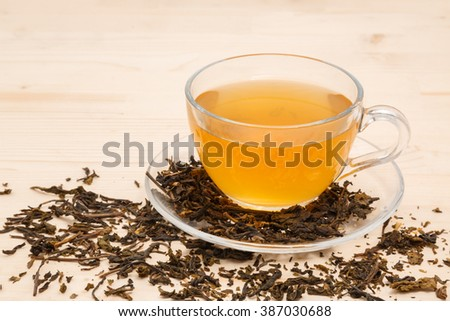 cup of tea and tea leaves on a wooden table