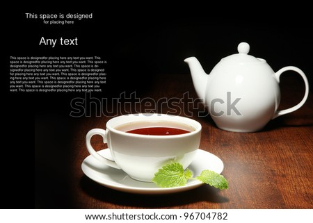 Cup of tea and teapot black background - stock photo