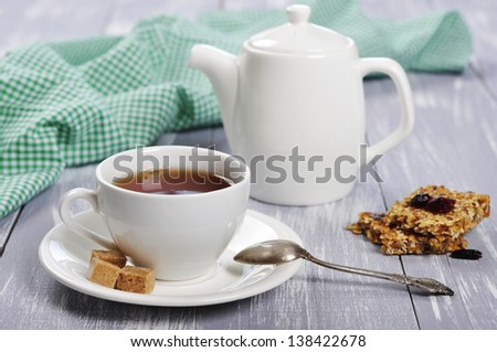Cup of tea and teapot on wooden background - stock photo