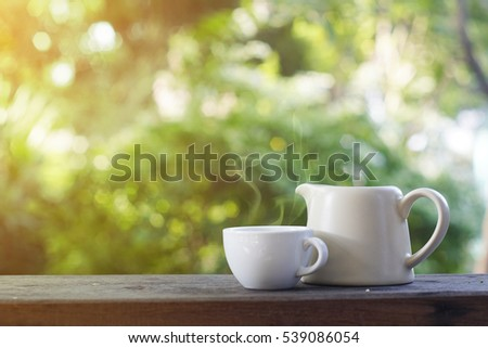 Cup of tea and teapot on wooden table