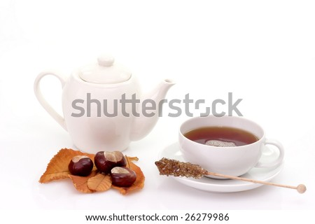 Cup of tea and teapot with autumn foliage on bright background
