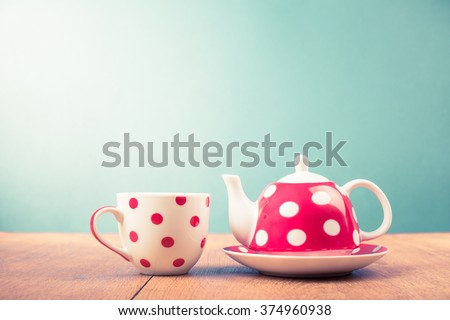 Cup of tea and teapot with polka dots. Retro style filtered photo - stock photo