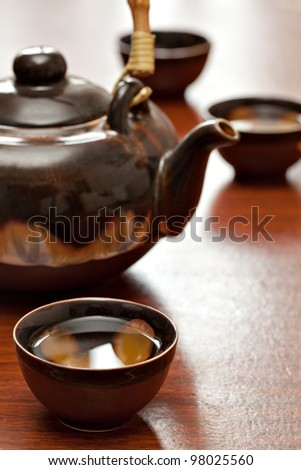 cup of tea and teapot, wooden desk