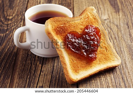 Cup of tea and toast bread with jam in shape of hearts on vintage wooden table - stock photo