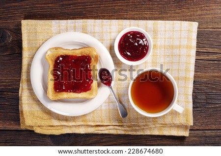 Cup of tea and toast with jam on yellow tablecloth. Top view - stock photo