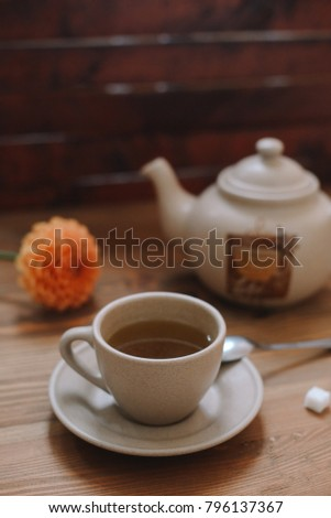 Cup of tea, colorful flower, teapot on the wooden brown background. Flat lay.