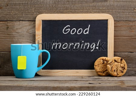 Cup of tea, cookies and blackboard with Good morning! phrase - stock photo