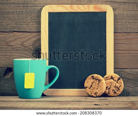 Cup of tea, cookies and small blackboard in retro style - stock photo
