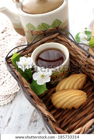 cup of tea, cookies and spring branch on wooden  - stock photo