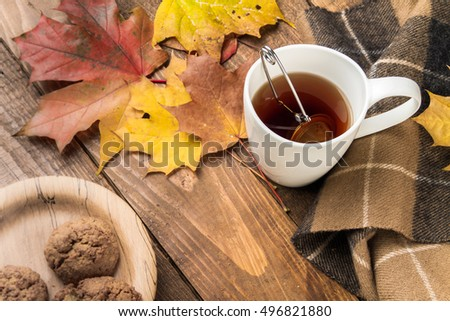 Cup of tea, homemade cookies, autumn maple leaves and woolen scarf on a wooden background.