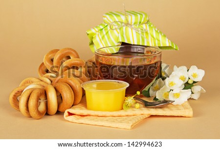 Cup of tea, honey, jam bank, a linking of bagels, flowers and a napkin on the beige