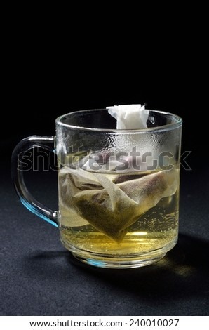 cup of tea infusion in a pocket in a transparent cup on black