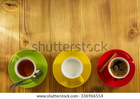 cup of tea, milk, coffee on wooden background - stock photo