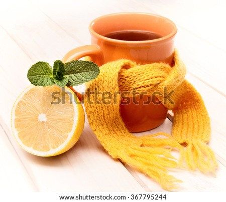 cup of tea, mint and lemon on a wooden table - stock photo