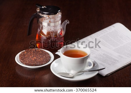 Cup of tea. newspapper and coockie on wooden table in coffeeshop. Shallow dof. - stock photo