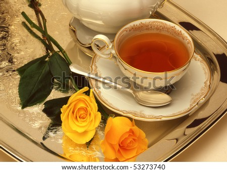 cup of tea on a tray with yellow roses - stock photo