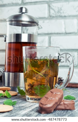 Cup of tea on a wooden background. Hot mint tea with chocolate and candy on old table