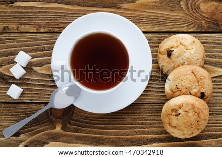 Cup of tea on a wooden table, sugar, spoon, cookies, top view