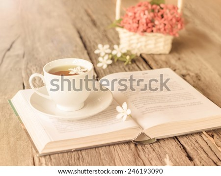 cup of tea on book with flower. - stock photo