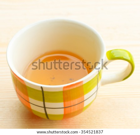 Cup of tea on bright wooden background