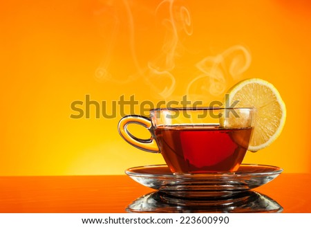 Cup of tea on glass with orange background - stock photo