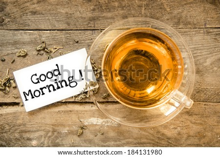 Cup of tea on table and paper sheet with text Good Morning