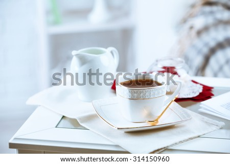 Cup of tea on table in living room - stock photo