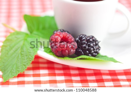 cup of tea,raspberry and  blackberry with leaves on plaid fabric