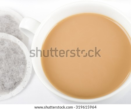 Cup of Tea - Simple cup of tea with milk and tea bags on a white background shot from above. - stock photo