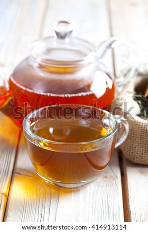 Cup of tea, teapot and dried tea leaves on wooden planks - stock photo
