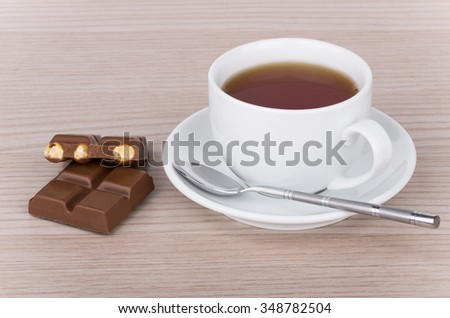 Cup of tea, teaspoon and chocolate pieces with hazelnuts on table - stock photo