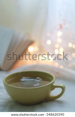 Cup of tea with a book and fairy lights in the background. Selective focus. - stock photo
