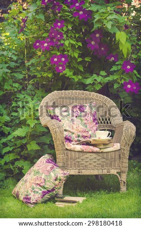 Cup of tea with a books on a chair in the garden.