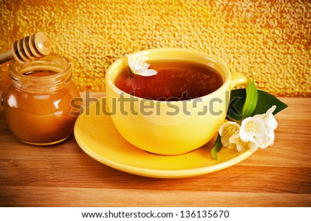 Cup of tea with a flower of a jasmin and honey - stock photo