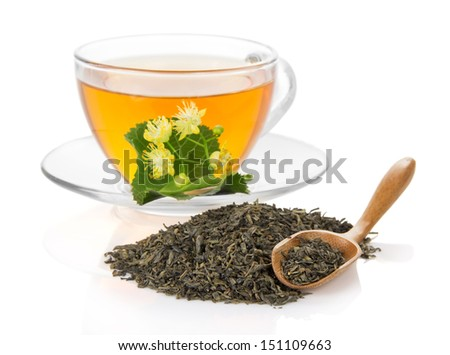 Cup of tea with a linden flower, a wooden spoon with the dry green tea isolated on the white