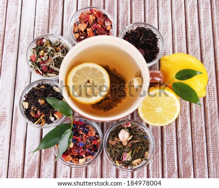 Cup of tea with aromatic dry tea in bowls on wooden background - stock photo