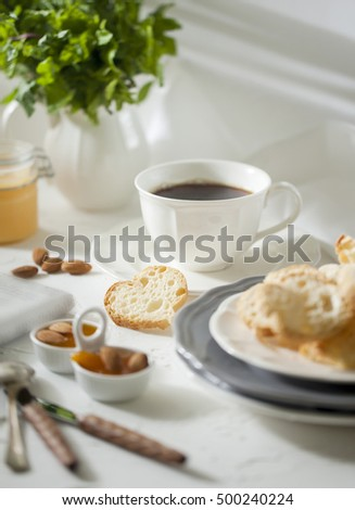 Cup of tea with biscuits and apricot jam on the white table with morning newspaper