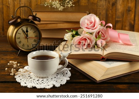Cup of tea with books and flowers on wooden background - stock photo