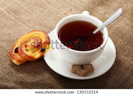 Cup of tea with buns on a natural tablecloth