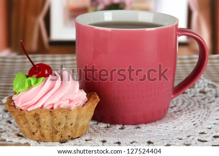 Cup of tea with cake on table in room