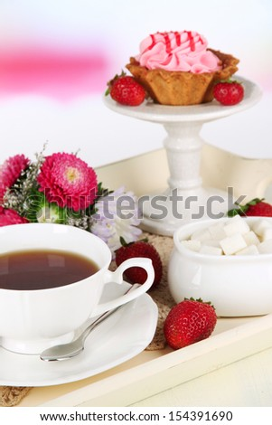 Cup of tea with cakes on wooden tray on table in room