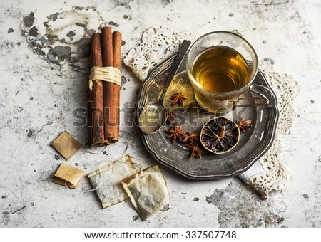 Cup of tea with cinnamon and anise on rustic white background