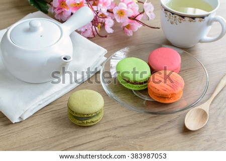 Cup of tea with colorful macaroons on wooden table