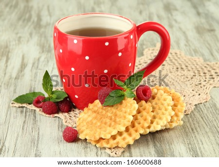 Cup of tea with cookies and raspberries on table close-up - stock photo