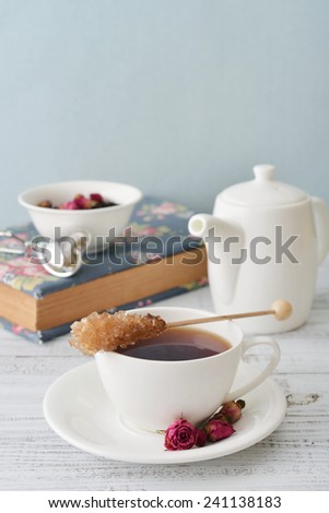 Cup of tea with dry rose buds and candy sugar over blue background